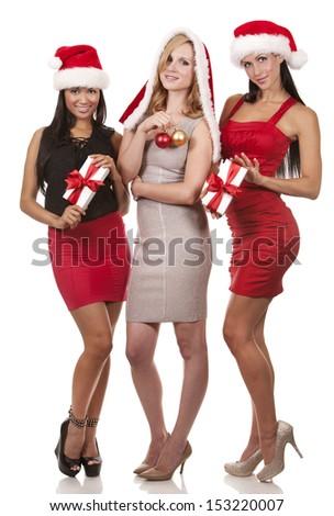 beautiful three women wearing christmas hats on white background - stock photo