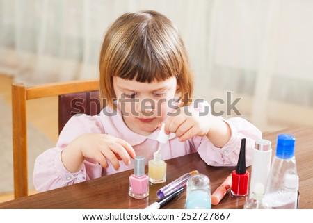 Beautiful three year old girl making manicure - stock photo