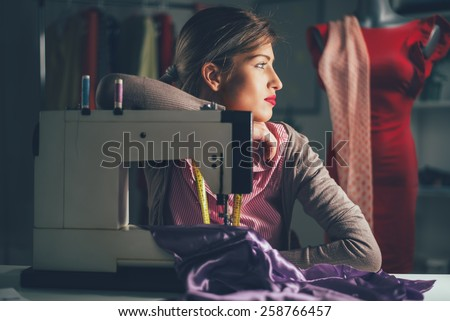 Beautiful tired woman sits in front of the sewing machine and thinking. Vintage concept. - stock photo