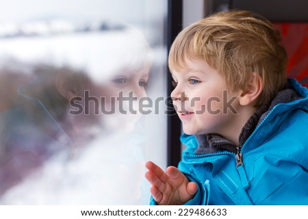 Beautiful toddler boy looking out train window outside, while it moving. Going on vacations and traveling by railway in winter. - stock photo