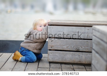 Beautiful toddler boy playing outdoors at the spring or summer day  - stock photo
