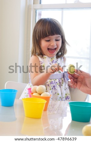 Beautiful toddler girl coloring eggs for Easter holiday - stock photo