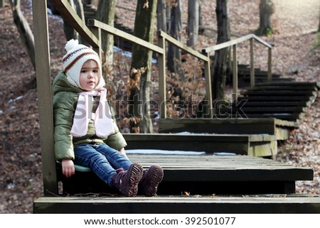 Beautiful toddler girl sitting on the wooden stairs in the park at first sunny spring day, happy family weekend - stock photo