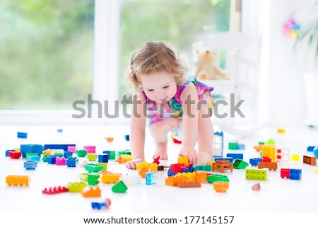Beautiful toddler girl with curly hair sitting on a floor in a toy mess in a sunny white bedroom with big windows with garden view playing with colorful construction blocks - stock photo