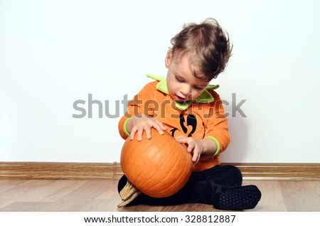 Beautiful toddler playing with a pumpkin preparing for halloween party - stock photo