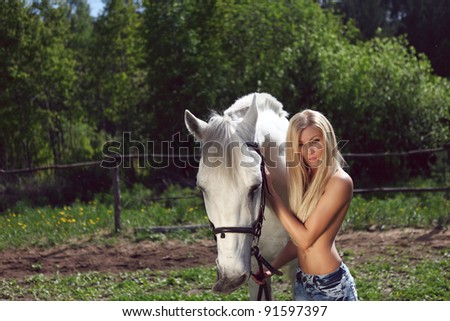 beautiful topless blond woman with a horse in the field - stock photo