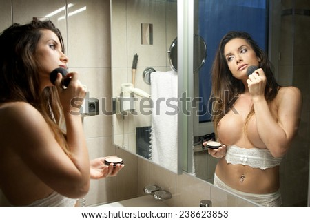 Beautiful topless woman applying makeup in front of the mirror - stock photo