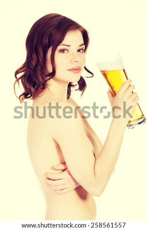 Beautiful topless woman is holding glass with beer. - stock photo