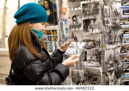 Beautiful tourist in Paris choosing souvenir postcards - stock photo