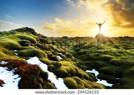 Beautiful tourist posing in the amazing volcanic mossy landscape of Eldhraun at sunrise in Iceland - stock photo