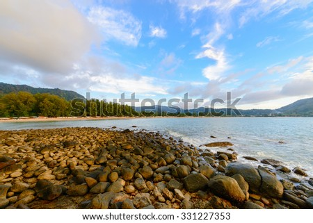 Beautiful tranquil cool natural rocky sea shore with fantastic views of the mountains with blue sky and clouds. - stock photo