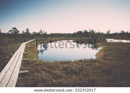 Beautiful tranquil landscape of misty swamp lake with mist and boardwalks. Vintage effect. - stock photo