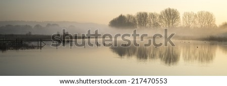 Beautiful tranquil panorama landscape of lake in mist - stock photo