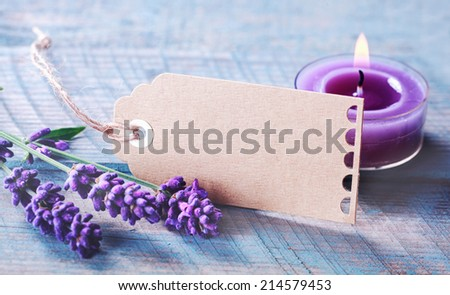 Beautiful tranquil spa and zen background with spikes of fragrant purple lavender and a burning aromatherapy candle on a rustic wooden background with a blank gift tag for your message - stock photo