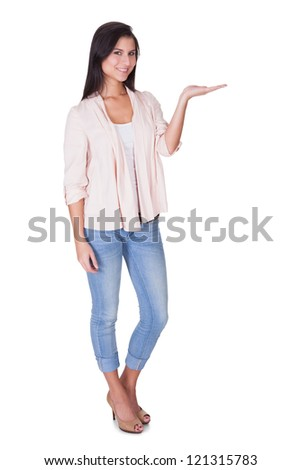 Beautiful trendy woman standing in a relaxed position with an empty palm extended in front of her isolated on white - stock photo