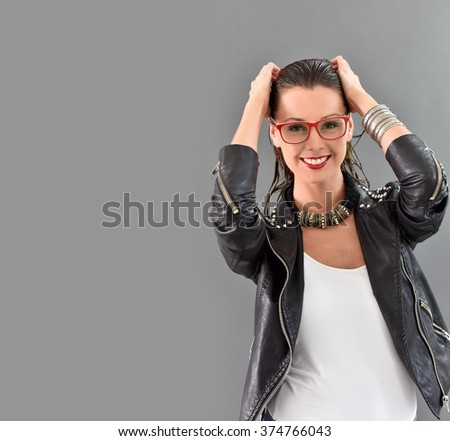 Beautiful trendy woman with red eyeglasses, grey background - stock photo
