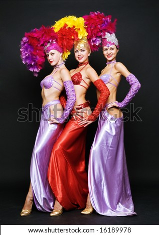 beautiful trio in stage costumes over dark background - stock photo