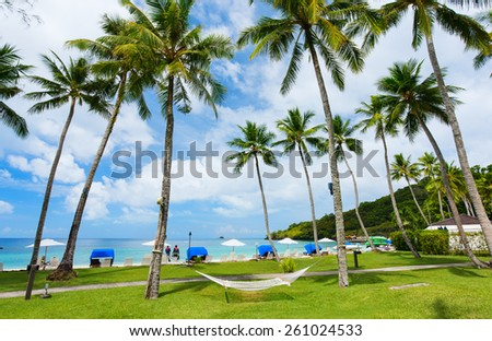Beautiful tropical beach with palm trees, white sand, turquoise ocean water and blue sky at exotic island - stock photo