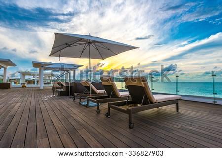 Beautiful tropical, caribbean wooden, flooring ocean beach, resort at sunset, evening, sunrise time. - stock photo