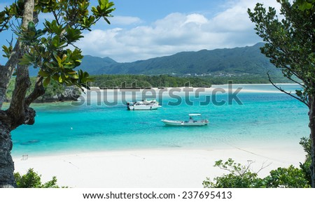 Beautiful tropical lagoon seascape with two boats in crystal clear water in Okinawa, Japan - stock photo