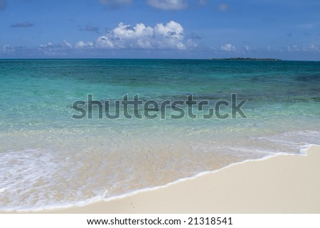 Beautiful tropical shoreline with clear green water and wave rolling up on white sandy shore. - stock photo