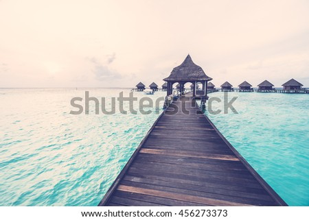 Beautiful tropical Sunset over maldives island with water bungalow in hotel resort - Vintage Filter and Boost up color Processing - stock photo
