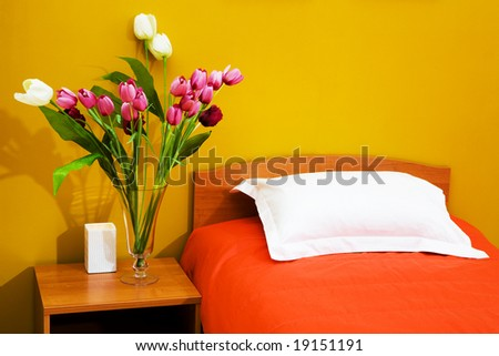 Beautiful tulips at a bed with an orange coverlet - stock photo