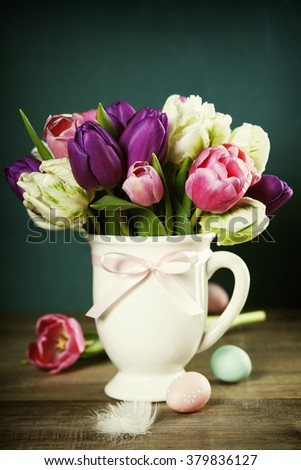 Beautiful tulips bouquet and easter eggs on wooden table - spring, easter or gardening concept - stock photo