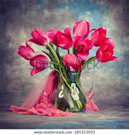 Beautiful tulips in a vase on the table. - stock photo