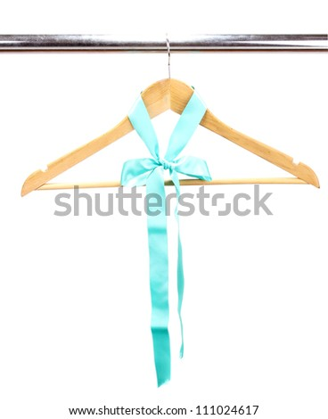 Beautiful turquoise bow hanging on wooden hanger isolated on white - stock photo