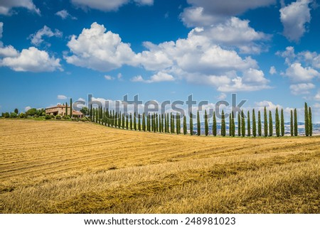 Beautiful Tuscany landscape with traditional farm house and dramatic clouds on a sunny day in Val d'Orcia, Italy - stock photo