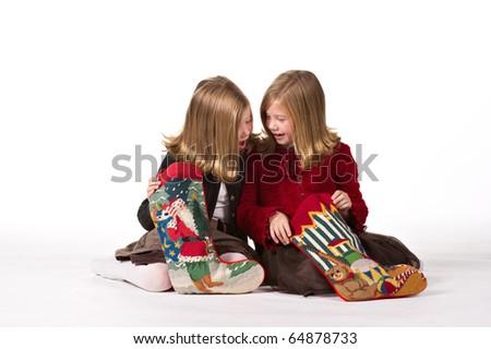 Beautiful twin sisters opening Christmas gifts - stock photo