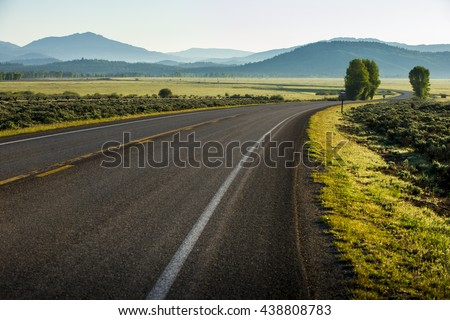 Beautiful twisting curving highway road drive in Tetons National Park with mountains and green scenery landscape - stock photo