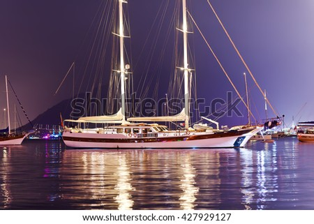 Beautiful two-masted yacht moored in the harbor in the evening. - stock photo