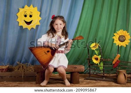 Beautiful Ukrainian girl playing the balalaika, rustic style, indoors - stock photo