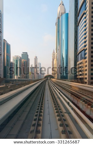 Beautiful, ultra modern architecture of Dubai, United Arab Emirates, in perspective from the rails of the city's metropolitan transit system. - stock photo