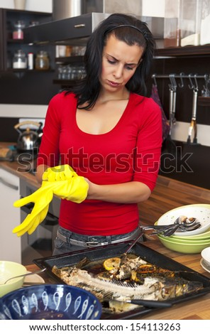 Beautiful unhappy woman preparing for cleaning  in kitchen - stock photo