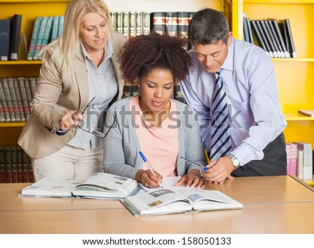 Beautiful university student writing in book while teachers assisting her at library - stock photo