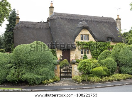 Beautiful upper class cottage with thatched roof and funny cut hedges in the village of Chipping Campden, Cotswold, United Kingdom. - stock photo
