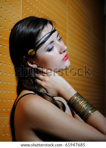 Beautiful upset girl with long hair and bright make-up touching her skin - stock photo