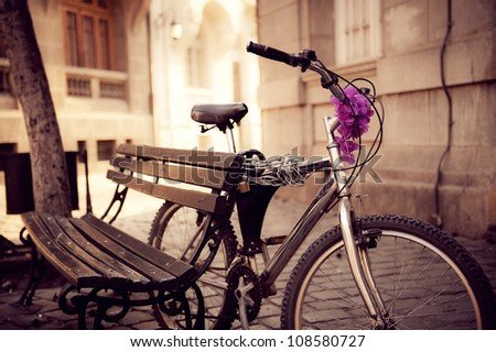 Beautiful urban bicycle secured on a bench. - stock photo