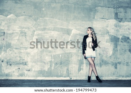 Beautiful urban girl leans against a concrete wall, cross processed image - stock photo