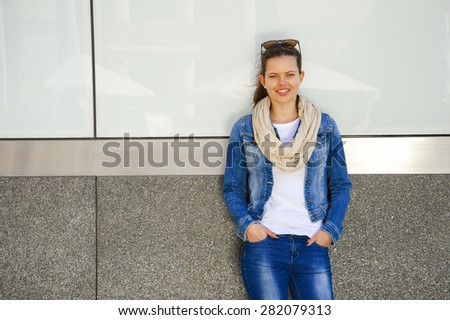 Beautiful urban woman, girl standing by the wall in city wearing jeans jacket - stock photo