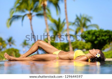 Beautiful vacation woman relaxing at a tropical spa resort lying on edge of infinity pool sunbathing in her bikini against a backdrop of palm trees. Pretty multicultural Asian Caucasian female model. - stock photo