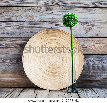 beautiful vase on abeautiful vase on a wooden plate with a flower on a wooden background wooden plate with a flower on a wooden background - stock photo
