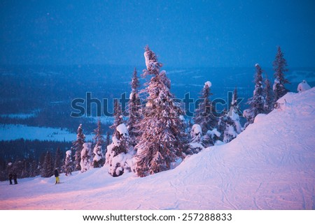 Beautiful vibrant night scandinavian Finnish swedish norwegian winter aerial landscape with slopes, skiing resort and cottages with lights - stock photo