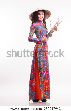 Beautiful Vietnamese young woman with ao dai  modern design long dress ( Ao Dai ) and palm-leaf conical hat ( non la ), holding cherry blossom on white background  - stock photo