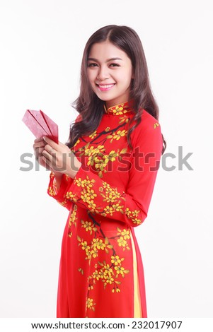 Beautiful Vietnamese young woman with red ao dai holding lucky red packet for celebrate lunar new year on white background  - stock photo
