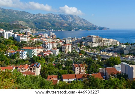Beautiful view from above of popular resort town of Becici on Adriatic coast against backdrop of sea and mountains, Montenegro - stock photo