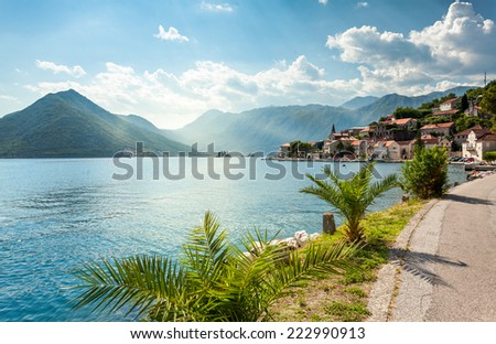 Beautiful view from embankment on sea bay surrounded by mountains at sunny day - stock photo